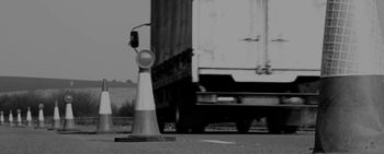 delivery truck driving safely around safety cone